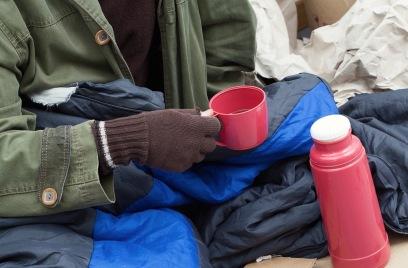 Beggar warming himself by a hot tea